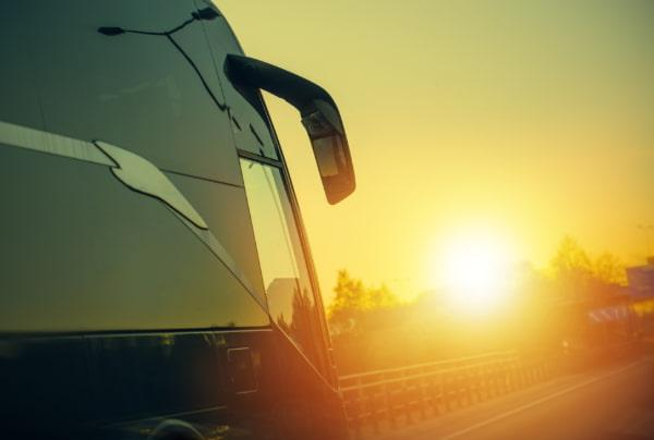 A charter bus drives on an empty highway, towards the sunset