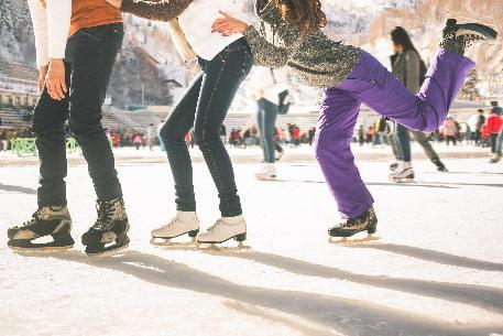 A line of ice skaters holding each others hips as they skate